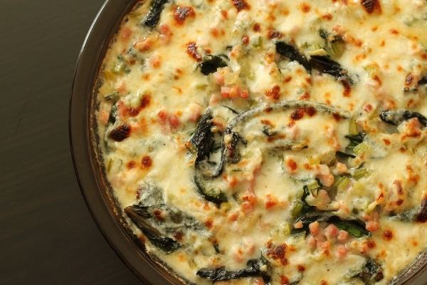 overhead view of a baked creamy gratin with pieces of diced ham and Swiss chard