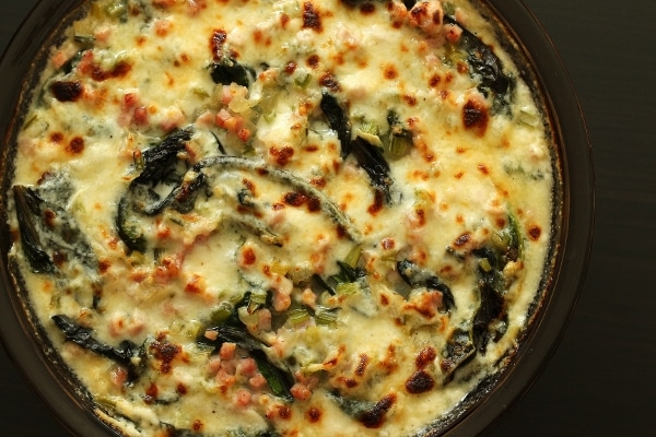 overhead view of a round baking dish of Swiss chard and ham in a creamy sauce