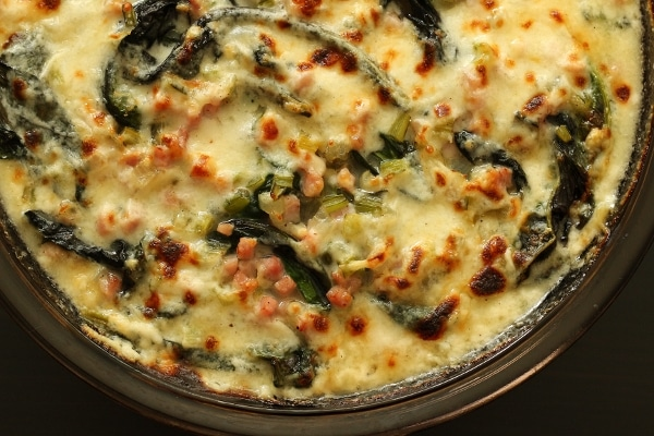 a round baking dish filled with creamy gratin of Swiss chard and diced ham