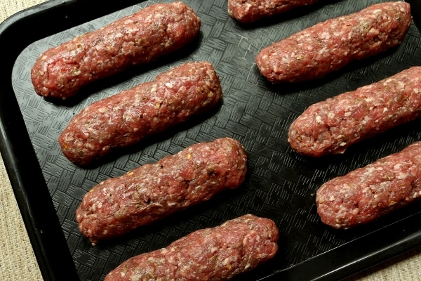 raw skinless sausages arranged on a black tray