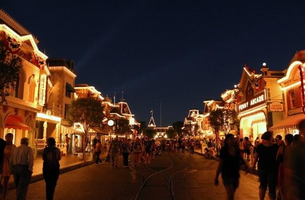 A group of people walking down Main Street U.S.A. at Disneyland at night