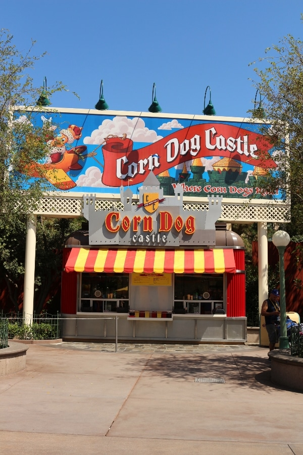 A sign that says Corn Dog Castle over a small building with a striped awning