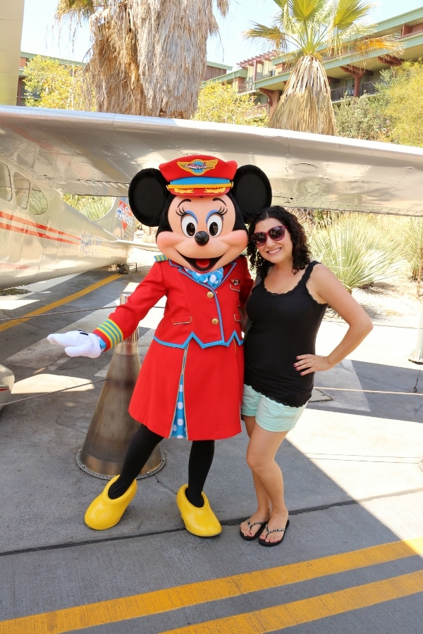 A woman posing with Minnie Mouse who is dressed like a flight attendant