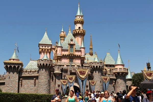 A group of people standing in front of Sleepy Beauty Castle at Disneyland Park