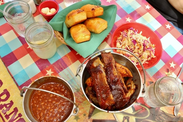 overhead view of buckets of ribs and beans, a bowl of coleslaw and basket of cornbread