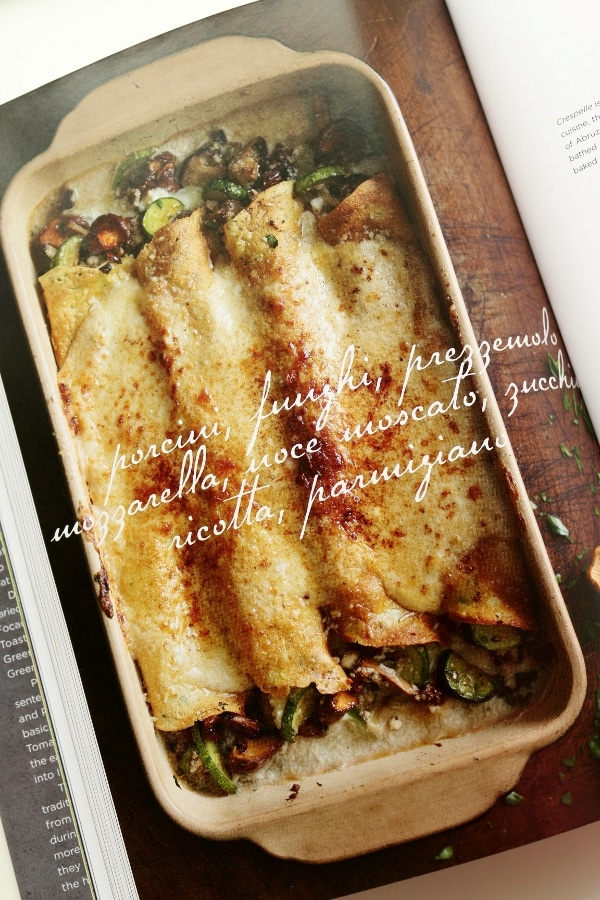 a rectangular casserole dish with four rolled crepes with vegetables coming out of the sides