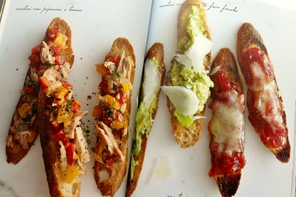 overhead view of long bread toasts with various toppings on a white background