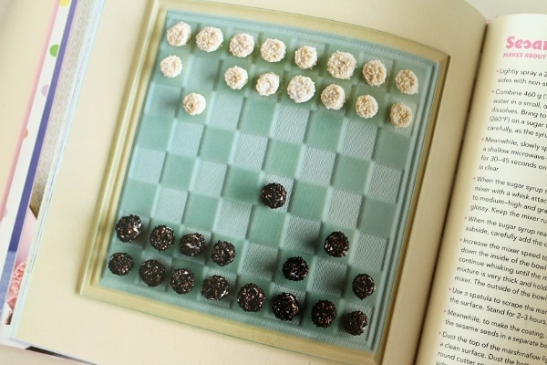 small black and white marshmallows arranged on a blue checkerboard