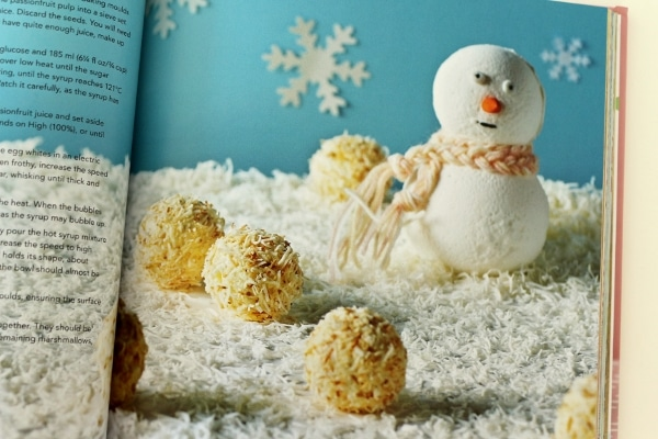 round toasted coconut balls next to a snowman figure with a blue background