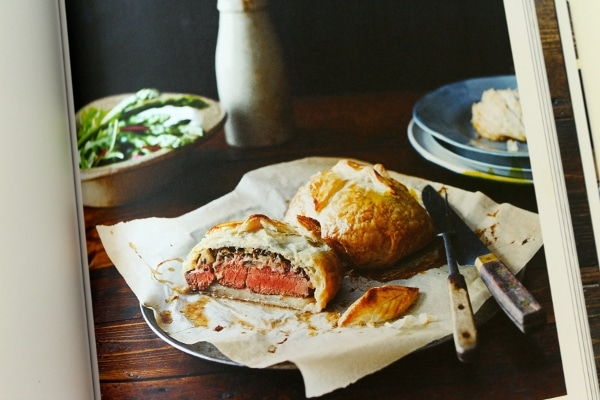 a plate of half-eaten beef wellingtons with pastry filled with rare filet mignon