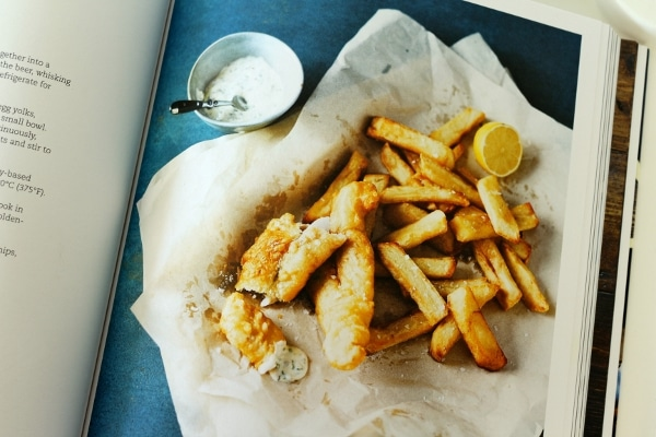 fish and chips on a was paper surface with a small bowl of tartar sauce