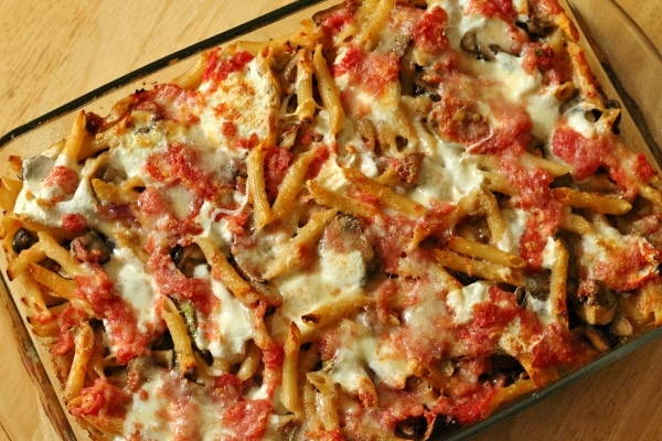 overhead view of baked penne pasta with tomato sauce and cheese in a glass dish