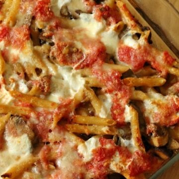 overhead view of a glass dish filled with baked pasta with cheese and tomatoes