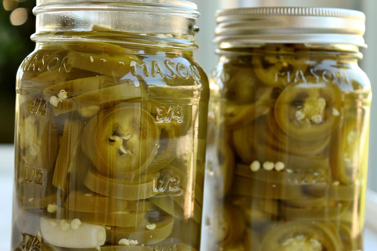 A closeup of 2 jars of pickled jalapenos side by side.