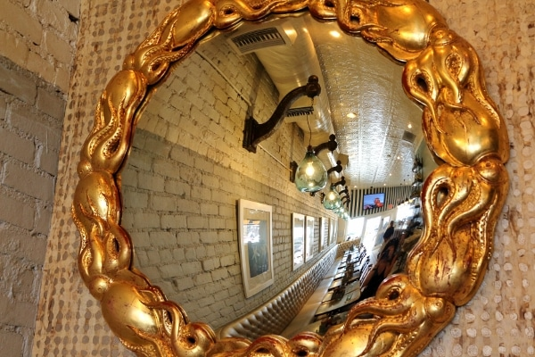 a reflection of a restaurant interior through a mirror with a gold octopus themed frame