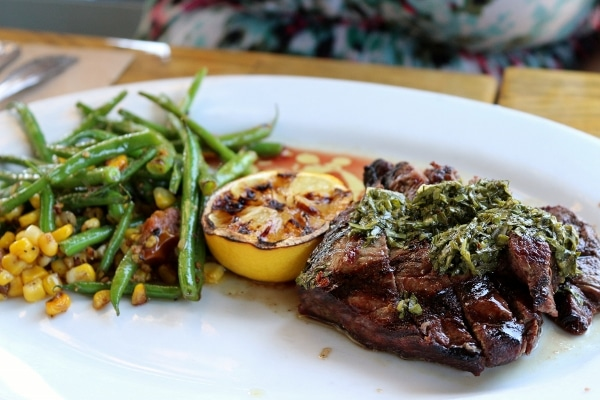 steak topped with green sauce on a white plate with green beans and grilled lemon