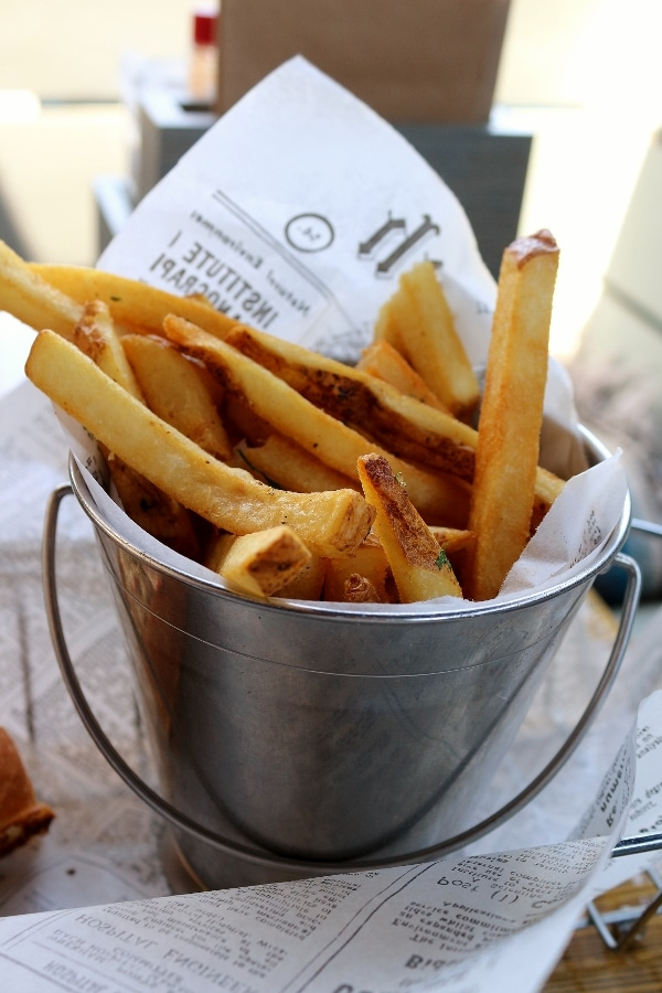 a small metal bucket filled with french fries