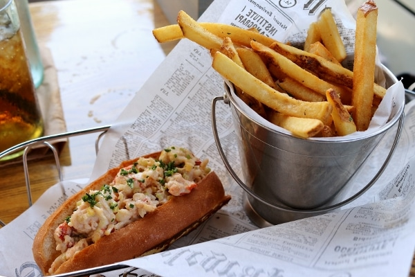 a lobster roll with a metal bucket of french fries served over a newspaper