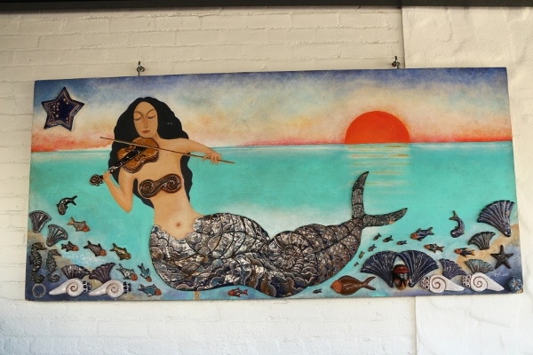 a painting of a mermaid playing the violin