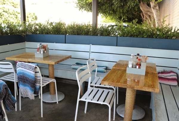wood outdoor restaurant tables with a blue booth seat and white chairs