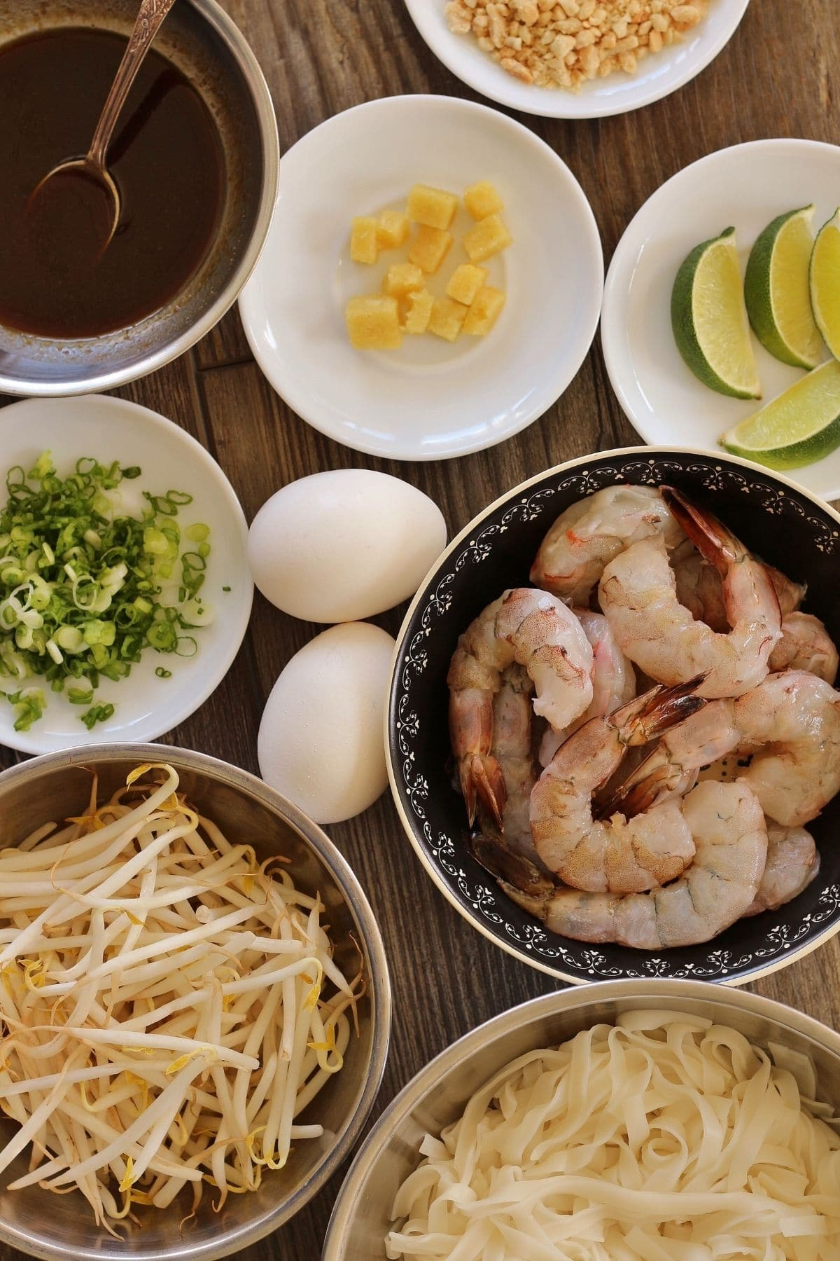 overhead view of ingredients for shrimp pad thai on plates and in bowls