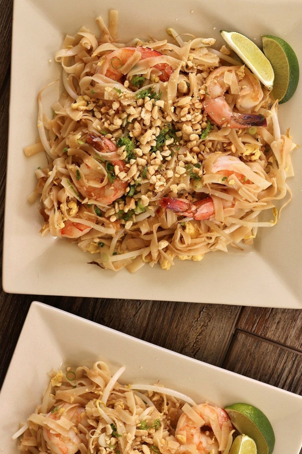 overhead view of shrimp pad thai noodles on two square plates