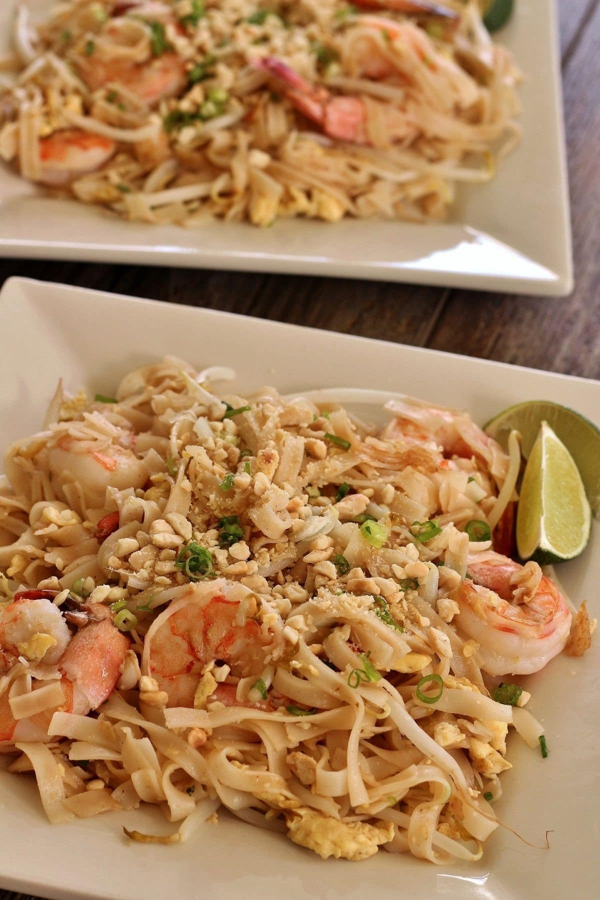side view of pad thai noodles with shrimp and chopped peanuts on two square plates