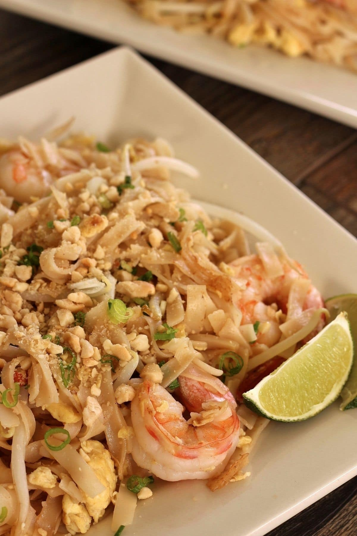 closeup of shrimp pad thai with chopped peanuts and lime wedges on a square plate