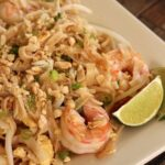 closeup of pad thai with shrimp on a square plate with lime wedges on the side