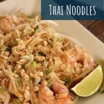 closeup of pad thai noodles with shrimp and lime wedges on a square plate