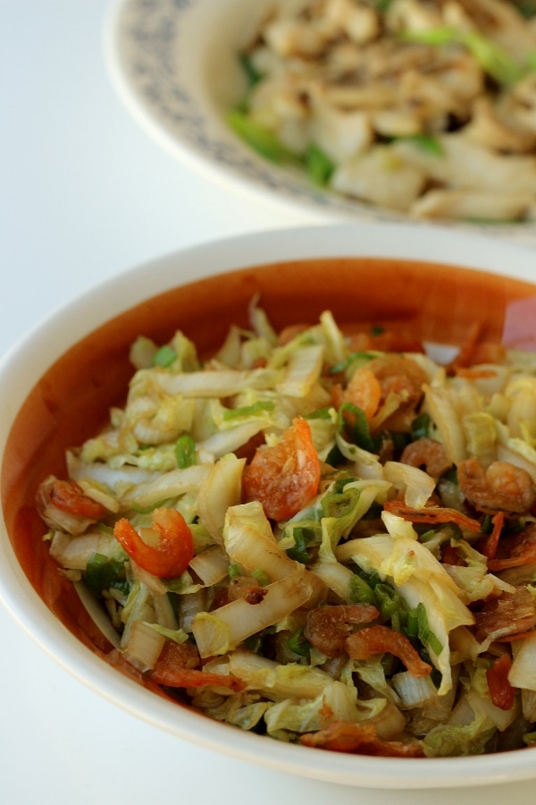 closeup of stir-fried cabbage with dried shrimp in a brown and white bowl