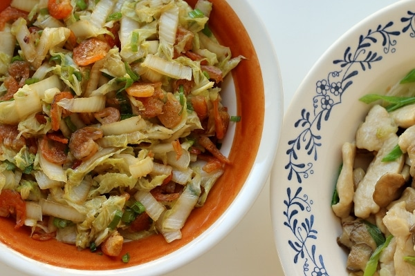 overhead view of two dishes of food including one with cabbage and dried shrimp