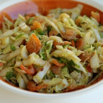 a brown and white bowl filled with stir-fried cabbage with dried shrimp