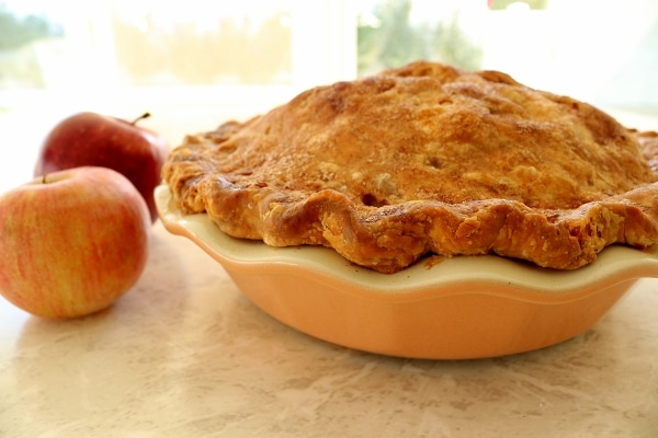 side view of an apple pie on a white table next to two fresh apples