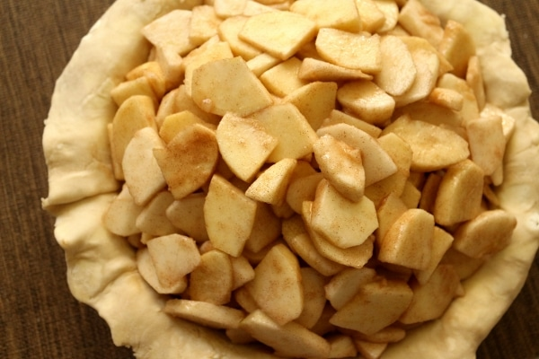 overhead view of a pie crust piled high with sliced apples