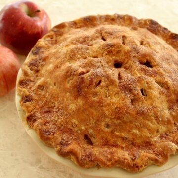 an apple pie on a white table with two apples next to it