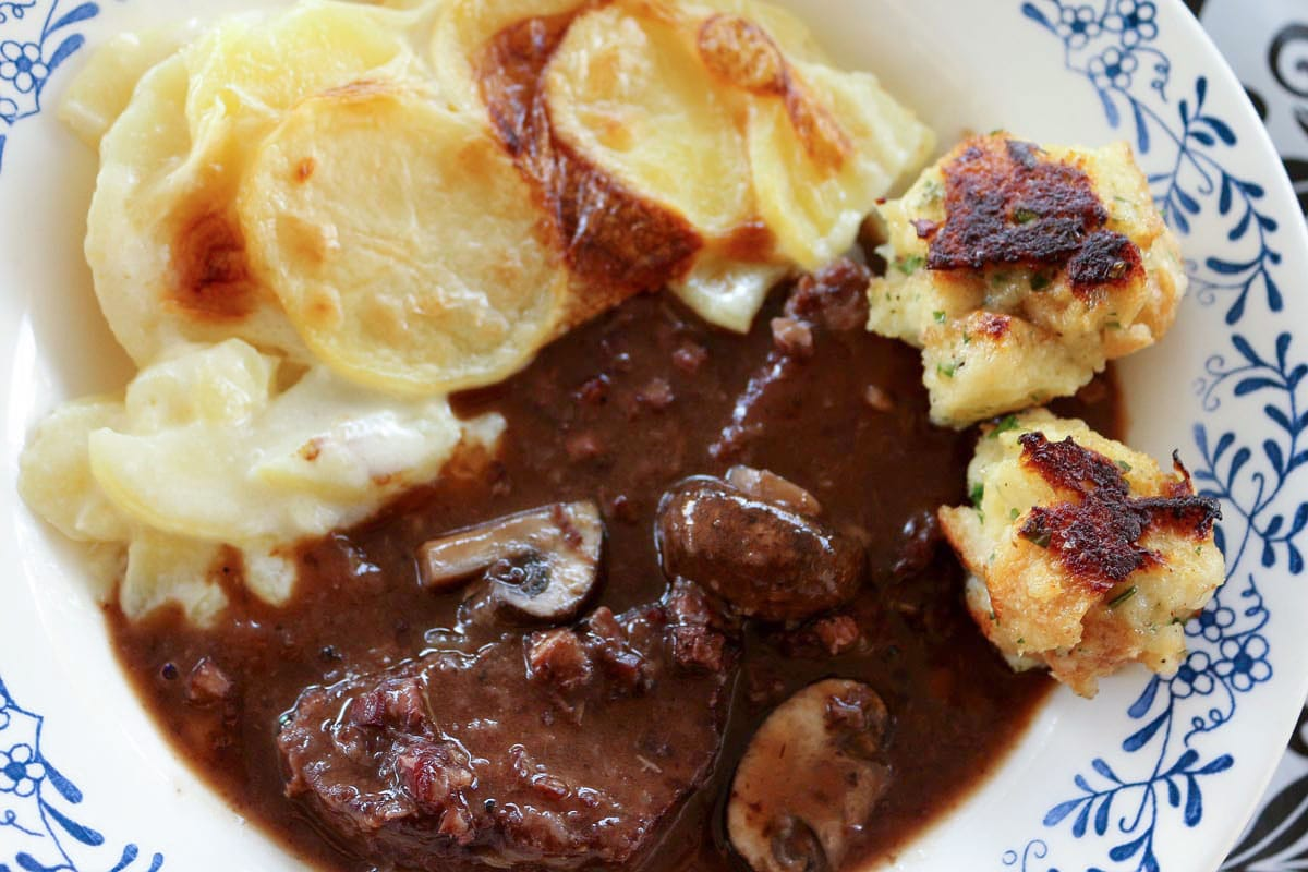 Beef bourguignon with baguette dumplings and potatoes dauphinoise in a wide bowl.