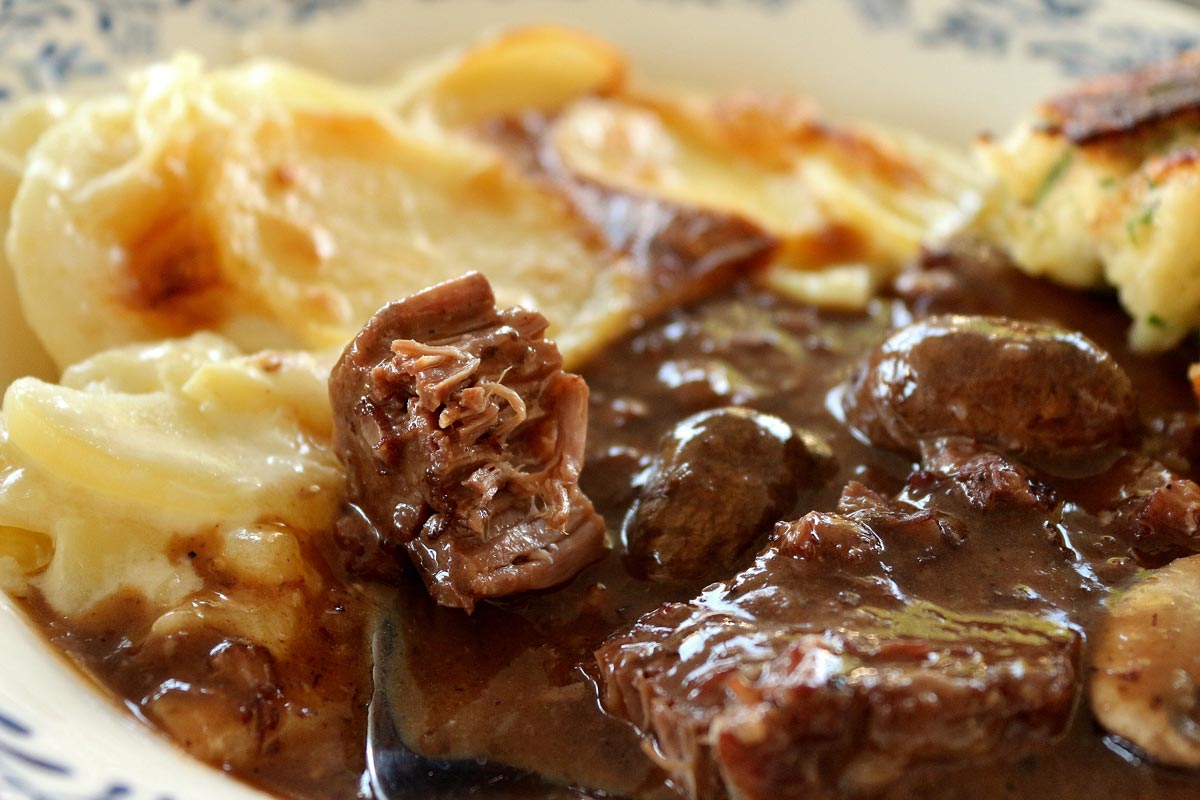 Closeup of a fork tender piece of beef in a bowl of beef bourguignon.