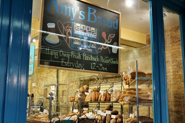 a chalkboard sign that says Amy\'s Bread hanging in a store window
