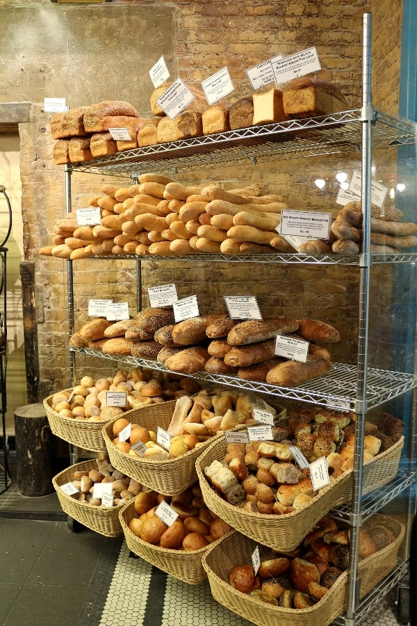 a display of bread on shelves and in baskets