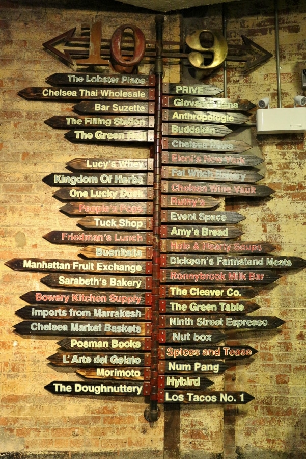 a wooden sign with names of businesses pointing in different directions
