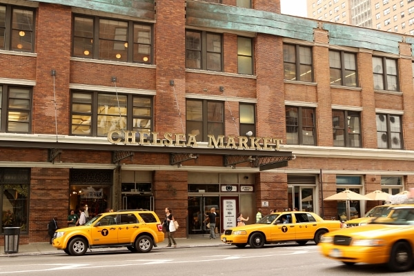 a large brick building with a sign that says Chelsea Market and yellow taxis in front