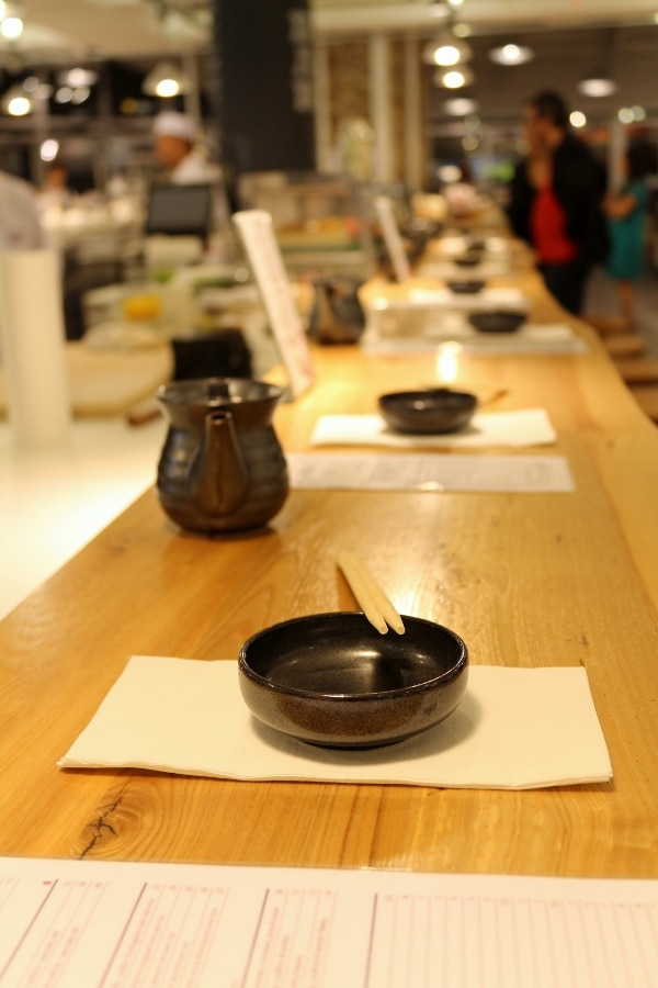 a long wooden surface with small bowls and chopsticks lined up at each place setting
