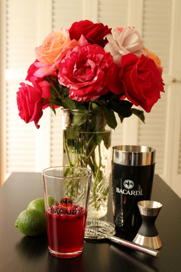 A bouquet of flowers in a vase on a table with a cocktail shaker in front