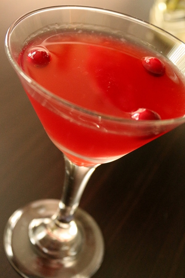 A closeup of a cocktail glass filled with a red drink with cranberries floating on top
