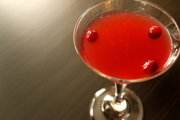 a red cranberry daiquiri in a cocktail glass on a dark table