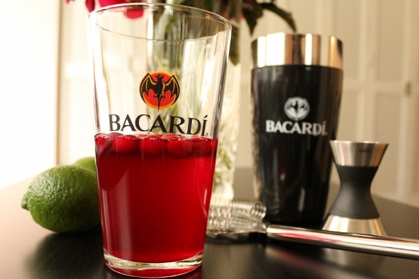 half-filled pint glass that says Bacardi on it on a black table next to limes
