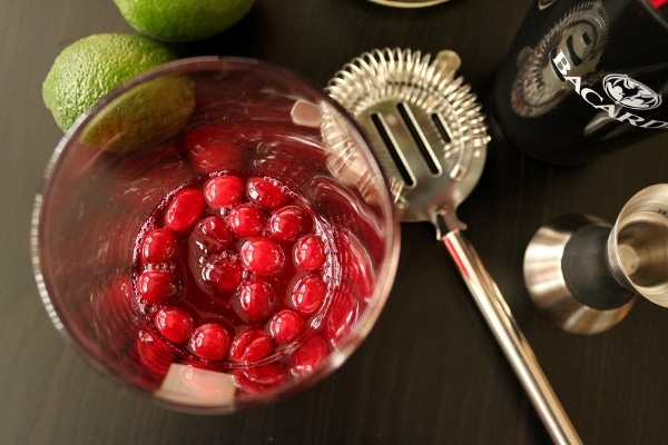 overhead view of a glass filled with cranberries in syrup next to a cocktail strainer