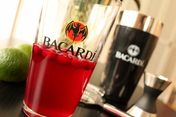 a closeup of a pint glass that says Bacardi half filled with red liquid
