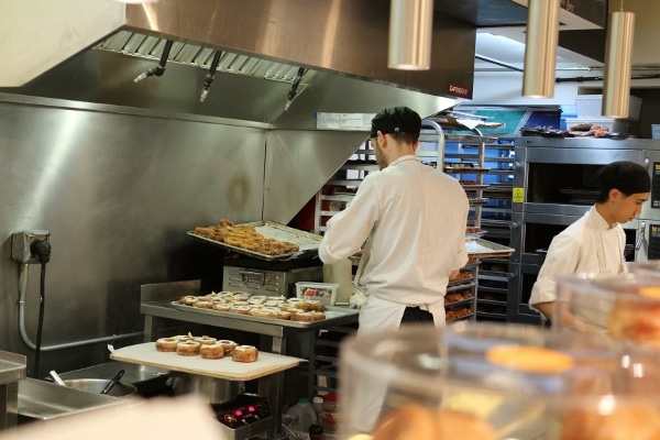 A group of people preparing food in a commercial kitchen